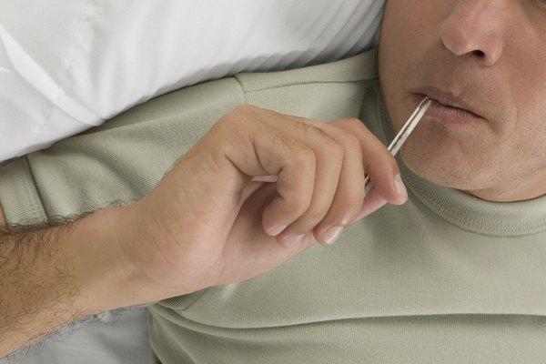 Mid adult man taking his temperature