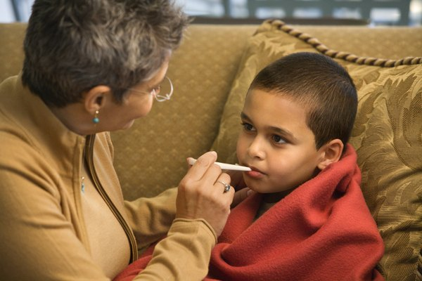 Grandmother taking grandson's temperature with thermometer