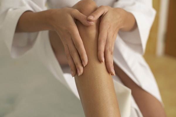 Woman putting lotion on her leg