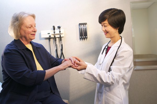 A doctor examines a mature woman's arm in the doctor's office