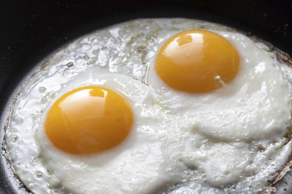 Closeup photo of two scrambled eggs in black frying pan