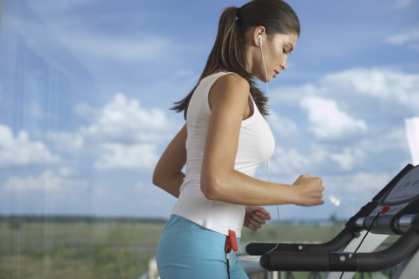 Woman jogging on treadmill by window with view of field with blue sky and clouds