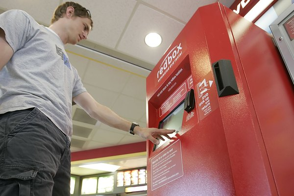 A young man taps the screen of a Redbox kiosk.