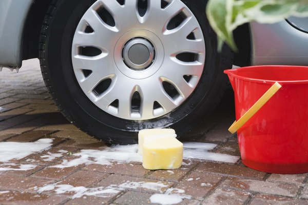 Car tire by a bucket of soapy water and sponge