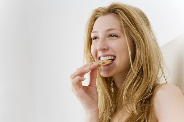 Woman eating cookie in bed