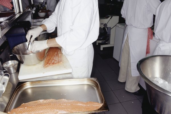 Chef preparing fish fillets in busy kitchen, mid section