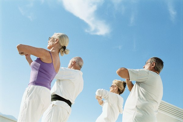 Four mature people practicing a martial art outdoors