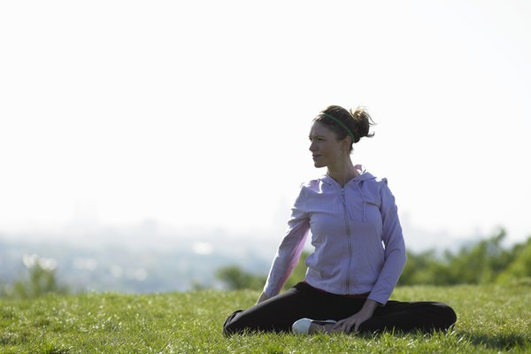 Young woman sitting on grass doing yoga