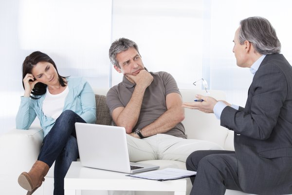 Mature Consultant Explaining To Couple