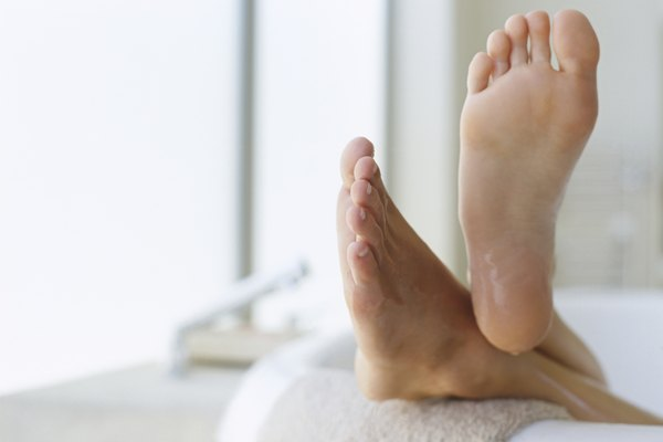 low section view of a person's feet resting on the edge of a bathtub