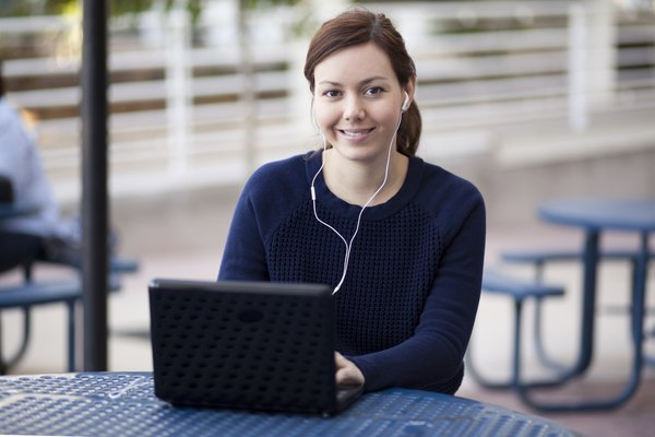 A young woman wearing headphones plugged into a laptop computer