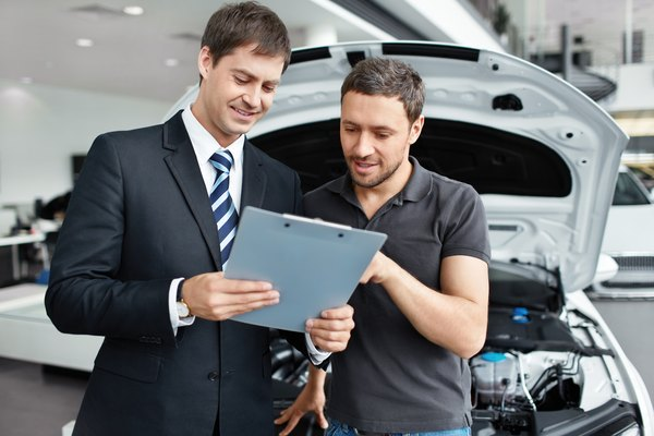 Men looking at clipboard in front of car with open bonnet