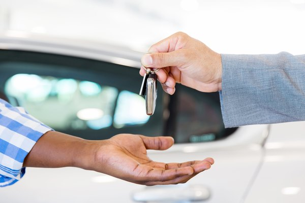 car dealer handing over new car key to customer
