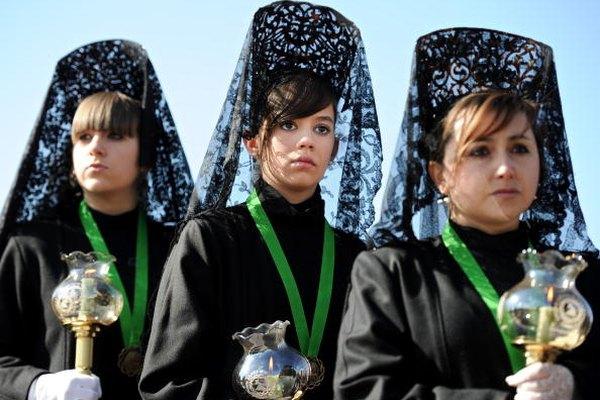 Mujeres usando mantillas de encaje negro sobre grandes peinetas durante la Semana Santa.