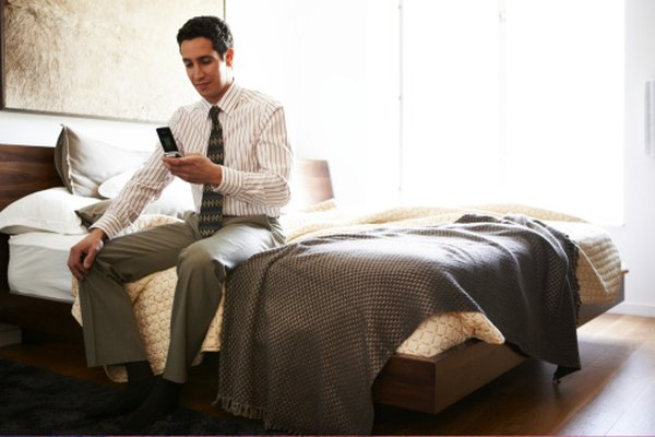Latino man in hotel bedroom on mobile phone