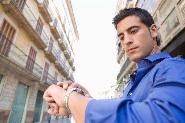 Un hombre mirando la hora en su reloj.