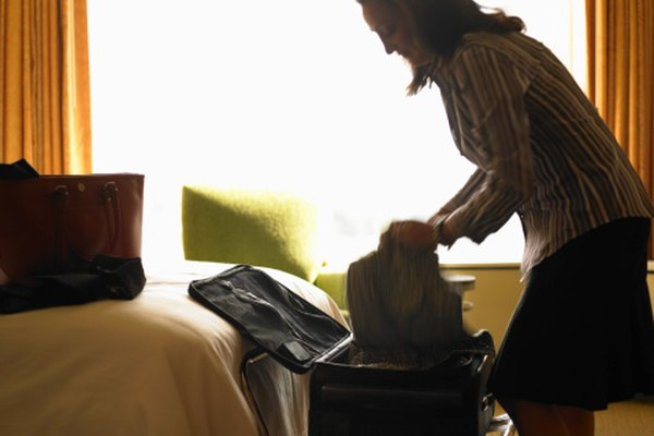 Mature woman unpacking suitcase in hotel room, side view