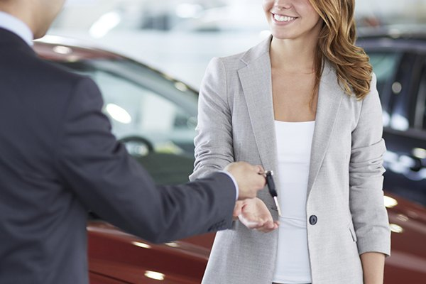 Excited man with car keys in showroom