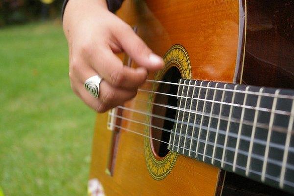 Una mujer toca la guitarra con su mano derecha