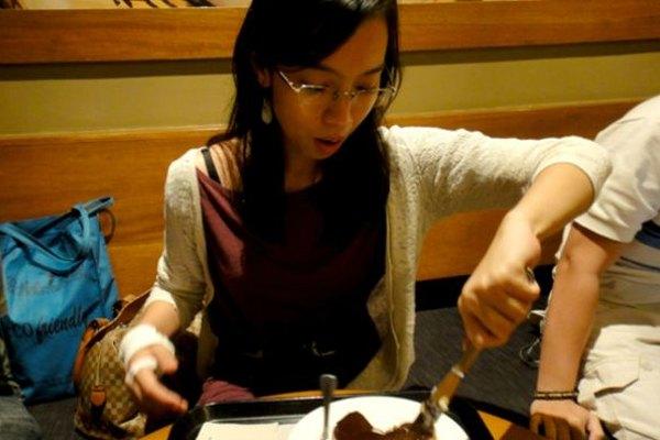 Una chica zurda intenta comer sin golpear con su codo a otra persona sentada al lado de ella