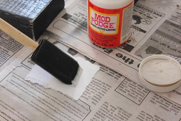 Aplica una capa fina de pegamento de decoupage a la parte trasera de la fotografía.