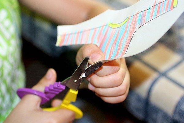 Un niño corta una hoja de papel con una tijera para diestros