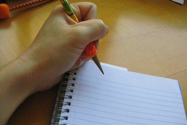 Un zurdo intenta escribir en un cuaderno con espirales