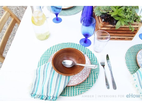Don't be afraid to mix patterns and textures: a turquoise striped napkin paired with a wooden bowl feels creative and unexpected.