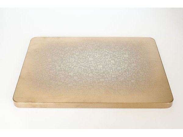 Gold spray paint adds new metallic shine to the edges of the tabletop.