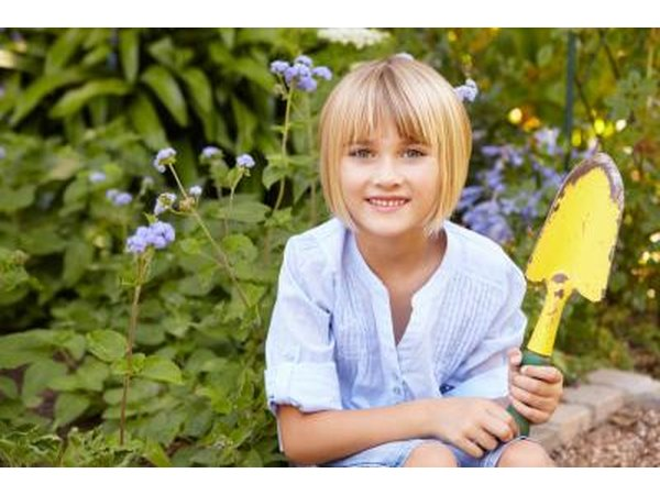 A girl holds a yellow spade in the garden.