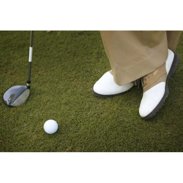 Golfer's shoes, club and ball on golf course.