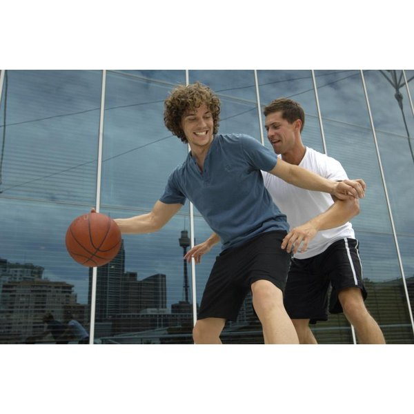 Two young men playing basketball together.