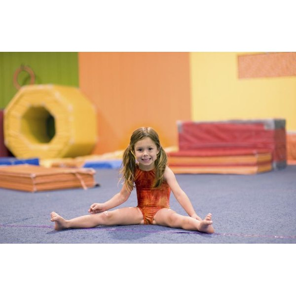 Young girl stretching during a gymnastics class.