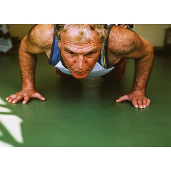 A close-up of a mature man doing push-ups on the gym floor.