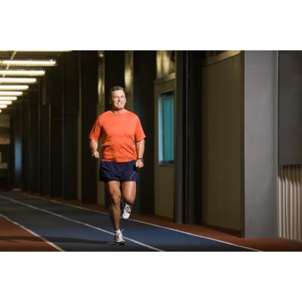 A man jogging on an indoor track.