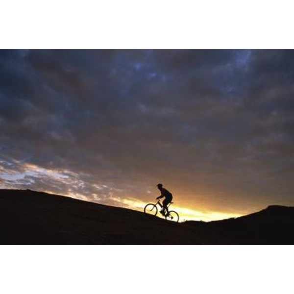 Someone is mountain biking in the sunset.