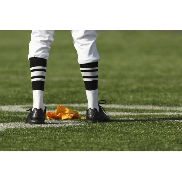 NFL Referee stands with a flag on the field