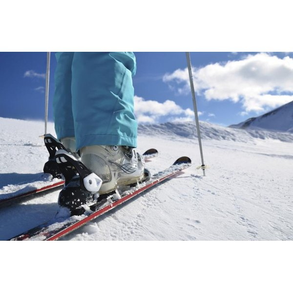 Woman wearing ski boots and skis at the top of a snowy mountain.