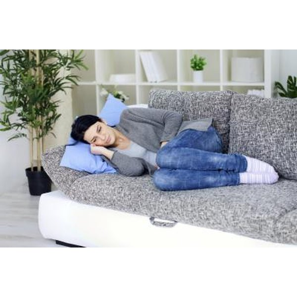 woman with abdominal pain on couch