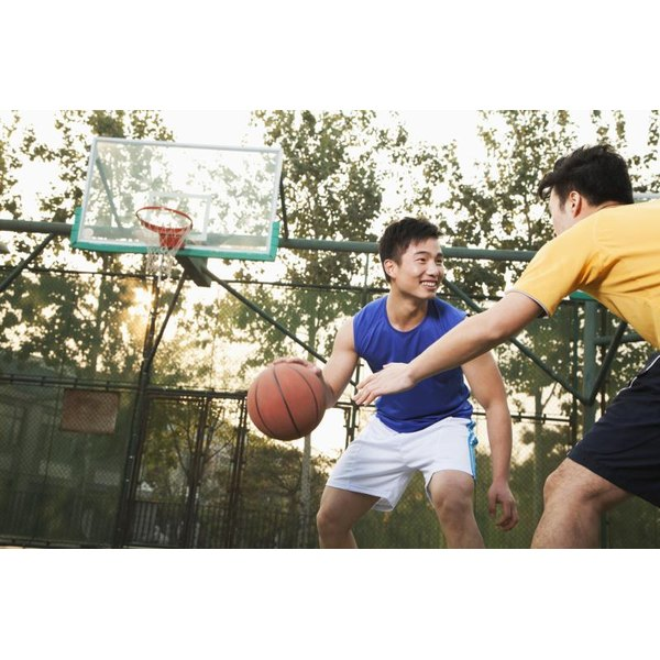 Two friends playing a game of basketball on an outdoor court.