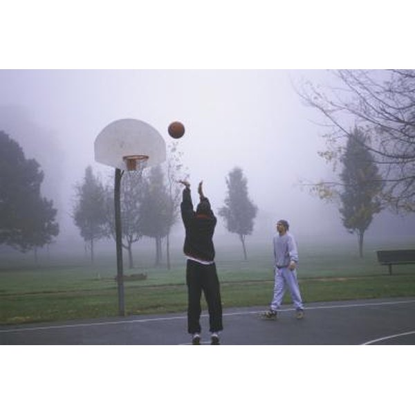 Man throwing a basketball as his friend watches on an outdoor court.