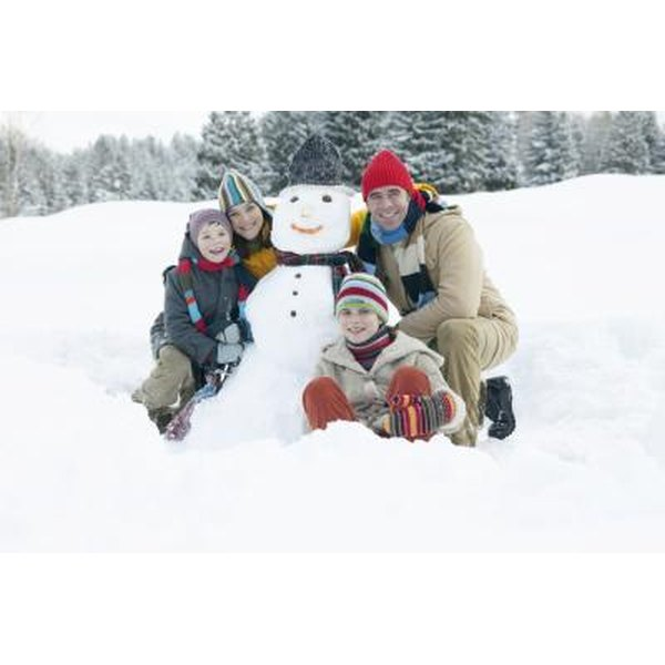 Family smiling around a snowman.