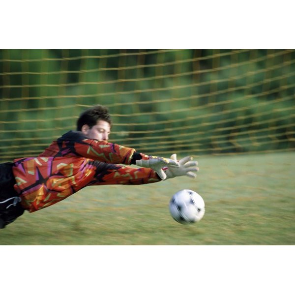 Soccer goalie diving to save a ball.