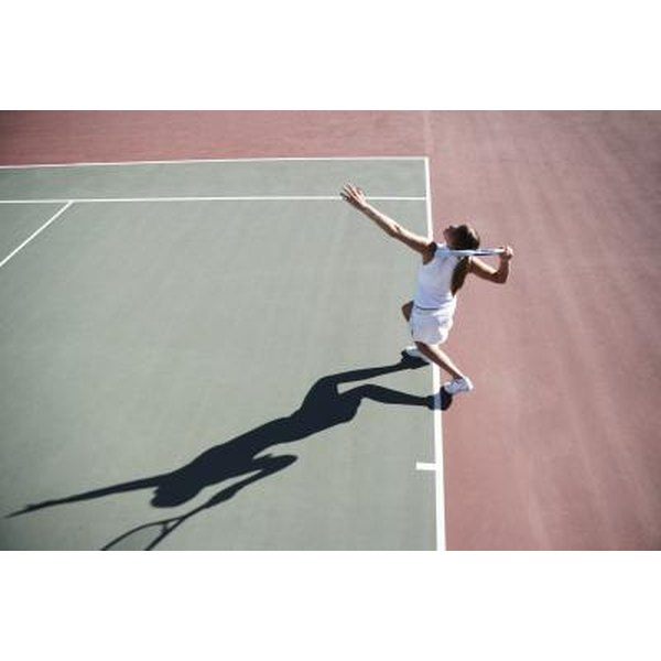 Woman playing tennis on tennis court.