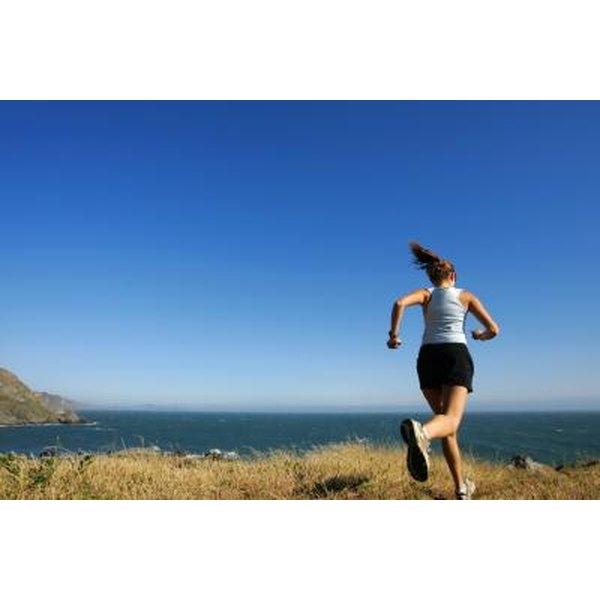 A woman is trail running outside.