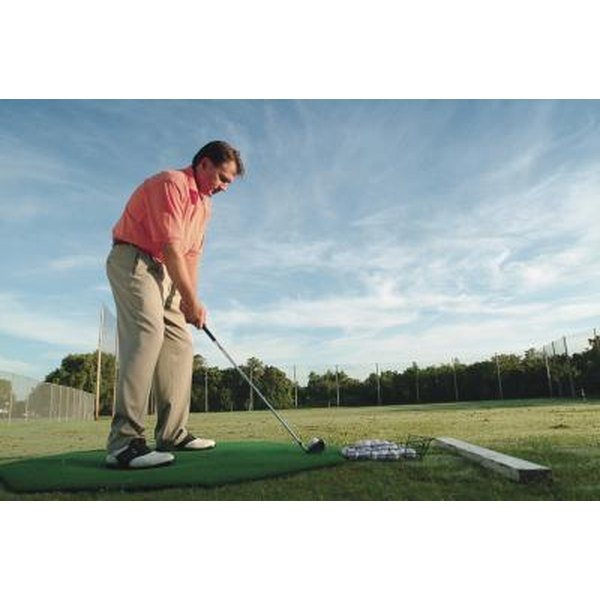 Man practicing his golf swing at a driving range.