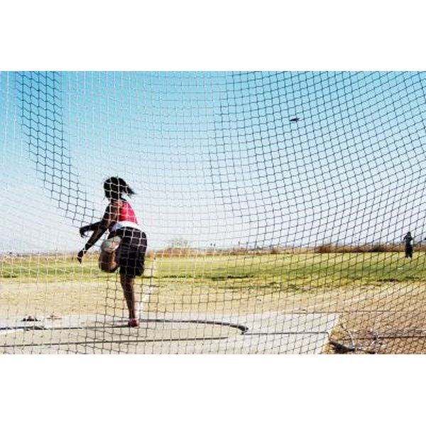 A discus thrower practices in a field.
