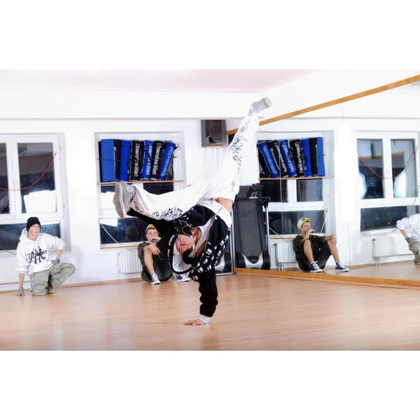 Three breakdancers practicing in a studio.