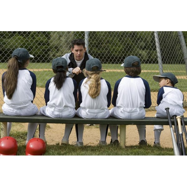 A coach talking to a little league baseball team.