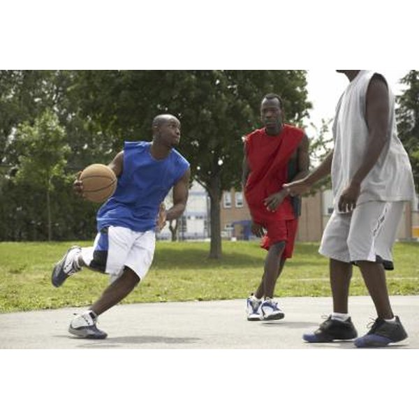 Men playing basketball on an outdoor court.
